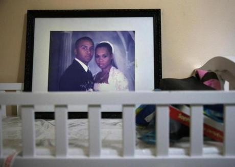 Kenny Fuchu keeps a wedding photograph of he and his deceased wife, Seveny, on their son's changing table at his home.
